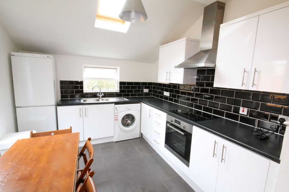 Kitchen with washing machine and tumble dryer